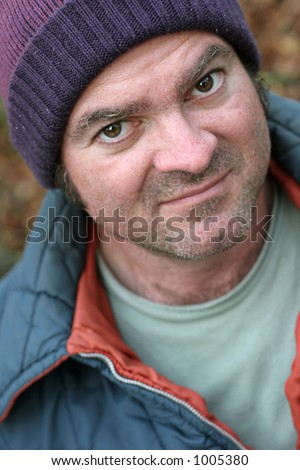 A closeup portrait of a homeless man.  Shallow depth of field, with focus on his left eye. - stock photo