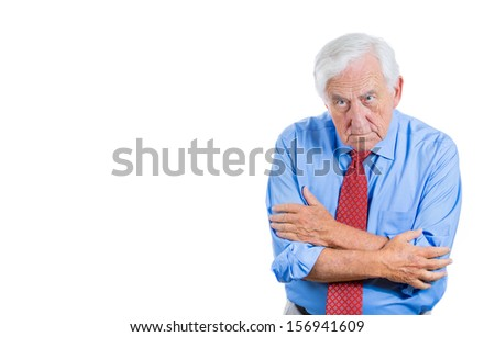 A closeup portrait of a serious senior businessman with a scowling expression on his face, isolated on a white background with copy space. Human emotions and facial expressions - stock photo
