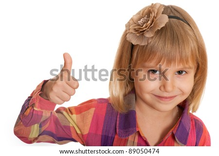 A closeup portrait of a smiling little girl holding her thumb up; isolated on the white background - stock photo