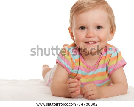 A closeup portrait of a smiling pretty little girl lying on white; isolated on the white background - stock photo