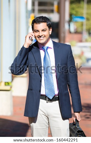 A closeup portrait of a young busy, happy, smiling business man talking on his phone while walking outside down the street holding a briefcase isolated on a background of a city. Corporate success - stock photo