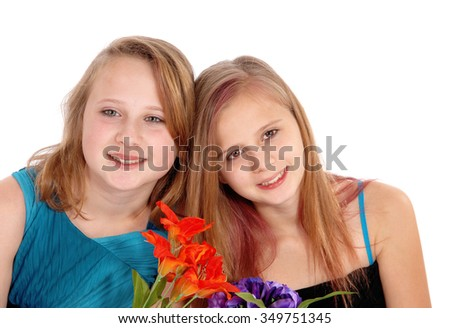 A closeup portrait picture of two sisters with blond hair, holding some