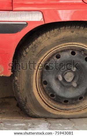 A closeup shot of a flat tire of a car - stock photo