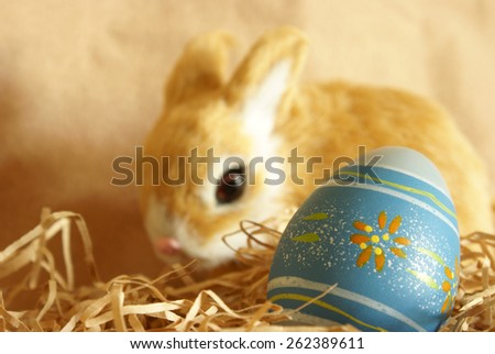 A closeup shot of an Easter Egg and bunny with the focus on the egg in the forground. - stock photo
