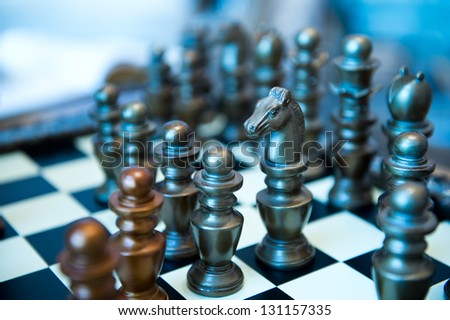 A closeup shot of chess pieces on a chessboard. - stock photo