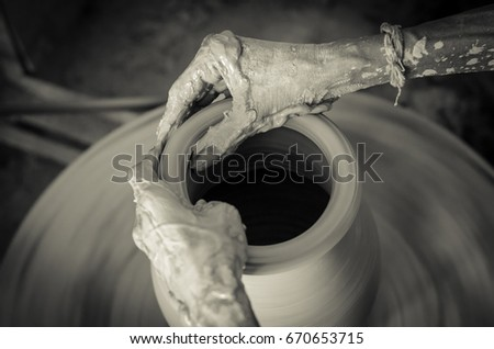 "a closeup shot of hands of a potter man making pots, vessels from mud also known as ""Matka"" in Indian Subcontinent in sepia tone"