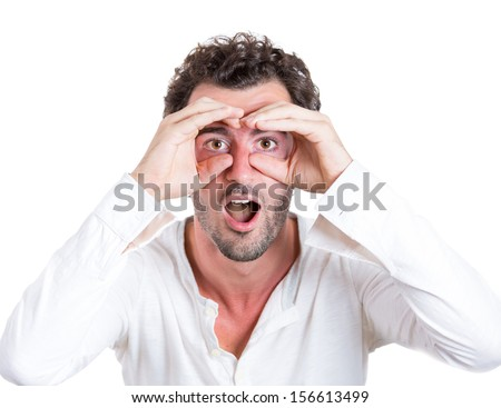 A closeup studio portrait of a young handsome, curious, surprised man looking through his fingers like binoculars, searching for something, looking for the future, isolated on a white background  - stock photo