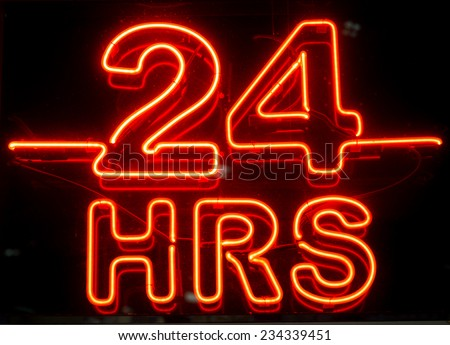 A closeup to a bright neon 24 hours sign at night - stock photo