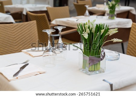 A closeup to part of a table at a restaurant in venice, showing, tablewear, glasses, chairs and flowers - stock photo