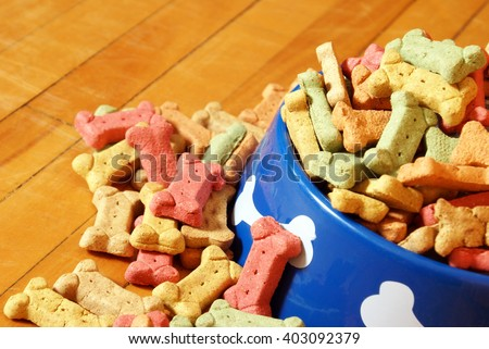 A closeup view of an abundant supply of dog treats overflowing his bowl on the hardwood floor of his domestic lifestyle. - stock photo