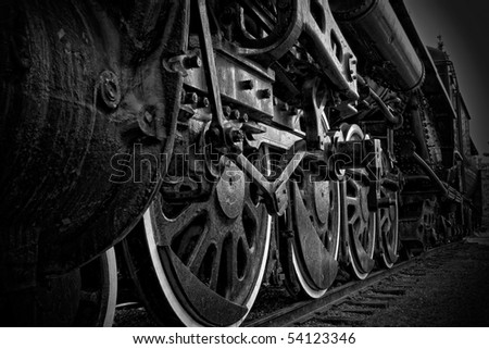 A closeup view of the wheels of an antique steam train, in black and white. - stock photo