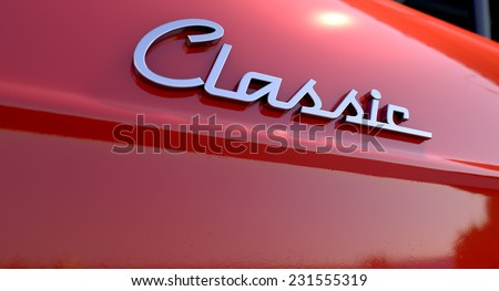 A closeup view of the word classic writting as a chrome emblem in a retro font set on a car painted in reflective red paint - stock photo