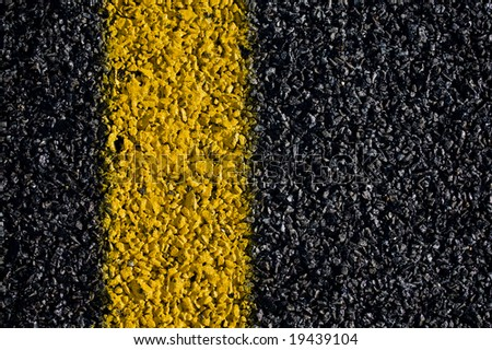 A closeup view of the yellow marking on a asphalt road.