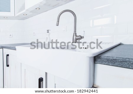 A closup of a sink and tap in new classic-look kitchen in modern rustic style in Krakow, Poland - stock photo