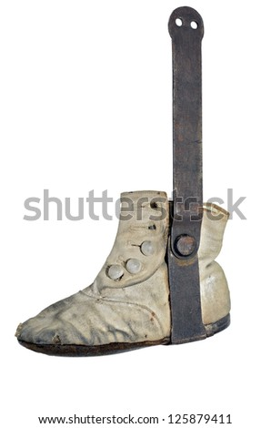 A cloth baby shoe with foot straightening device attached.  This was used in the 1900's and many times was left on the foot so long that it became deformed. - stock photo