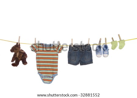 A clothesline used to dry infant clothing including shoes, socks, shirt, shorts and a teddy bear isolated on a white background.  Image was shot against a lighted white backdrop and is not a cutout.