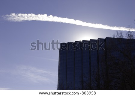 A cloud trails across the sky and a modern glass building shields the sun.