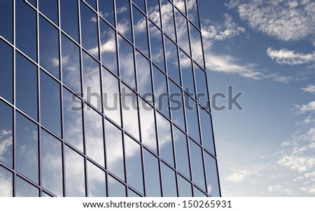 A clouds reflection in glass wall of business building - stock photo