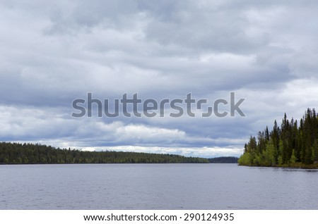 A cloudy day at the lake in Northern part of Finland. - stock photo