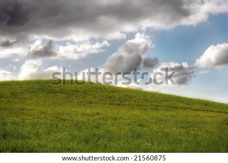A cloudy sky over a green field, windows style - stock photo