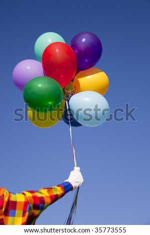 A clown holding a group of colorful balloons in front of a blue sky - stock photo