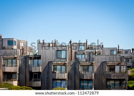 A cluster of modern style townhomes with balconies and wood siding. - stock photo