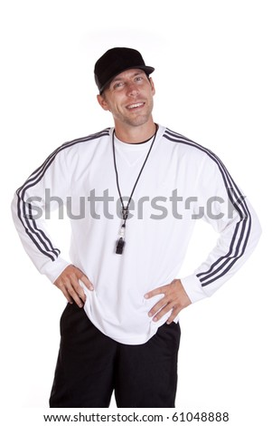 A coach is standing with his hands on his hips smiling. - stock photo