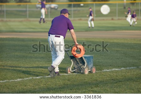 A coach prepares a high school baseball diamond for a game.