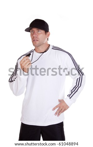 A coach standing with one hand on his hip holding a whistle. - stock photo