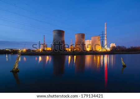 A coal-fired power station in river landscape with dead trees at night - stock photo