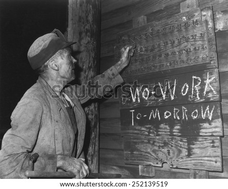 A coal loader putting up his check at the end of day's work on Friday, Sept. 13, 1946. 'No Work Tomorrow' with 'N' written backwards. Harlan County, Kentucky. Photo by Russell Lee. - stock photo