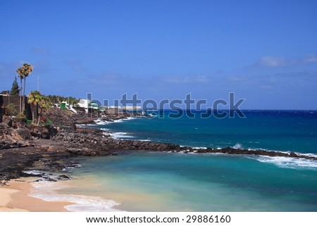 A coastal scene with a breakwater in Costa Teguise, Lanzarote - stock photo