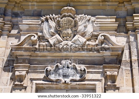 a coat of arms on top of an entrance made of limestone - stock photo