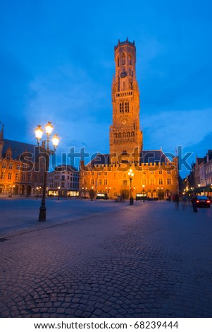 A cobblestone road leads to the belfry and clock tower at twilight blue hour in central old city of Bruges, Belgium - stock photo
