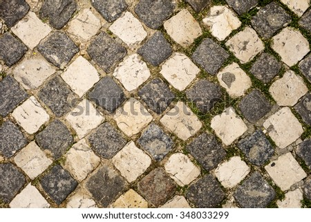 A cobblestone sidewalk in the Alfama neighborhood of Lisbon has arranged the light and dark stones in an alternating pattern like a checker board. - stock photo