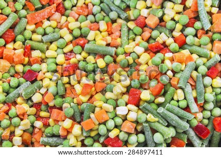 A cocktail of frozen chopped vegetables close-up as background - stock photo