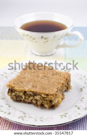 A coconut pecan blondie square on a plate with a cup of tea, vertical with copy space, shallow depth of field - stock photo