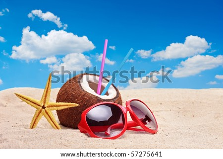 A coconut, starfish and a sunglasses on a beach - stock photo