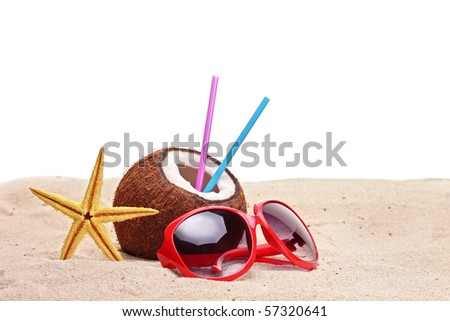 A coconut, starfish and a sunglasses on a beach against white background