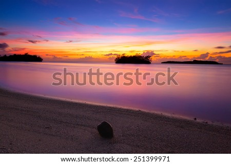 A coconut washed ashore as the tide retreated on the Guam coastline as the post sunset colors hit their peak. portrait orientation - stock photo