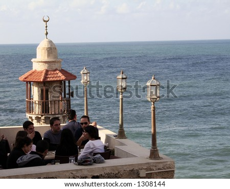 a coffee bar and a restaurant with a view to a mosque in jaffa israel - stock photo