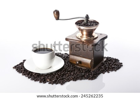 A coffee cup and coffee beans and grinder isolated white at the studio. - stock photo