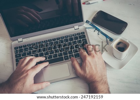 a coffee cup on white table and laptop - stock photo