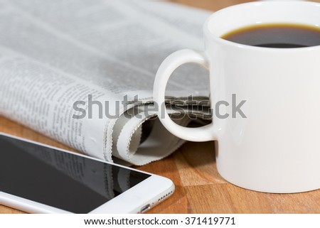 A coffee cup with a modern mobile phone on a wooden table. Also a newspaper is next to it.