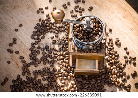 A coffee grinder and coffee beans with natural light