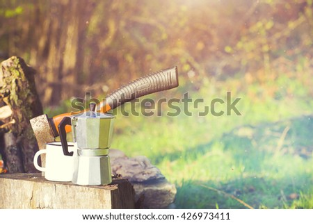A coffee maker and an axe near a fire in camping on the nature.