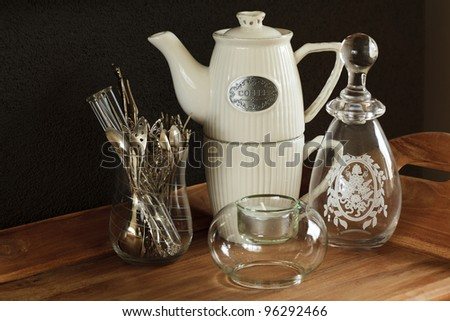 A coffee-pot, spoons, candle and vase on a wooden tray against a brown wall.