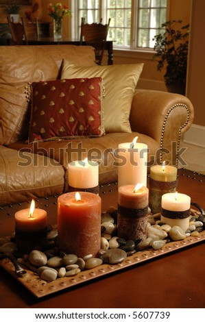 a coffee table with candles and a luxurious leather sofa