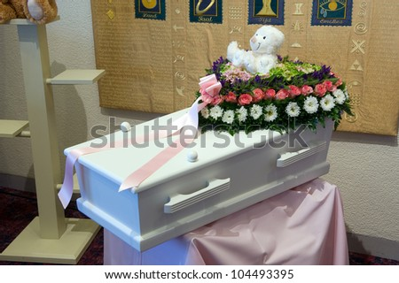 A coffin for a child with a flower arrangement - stock photo