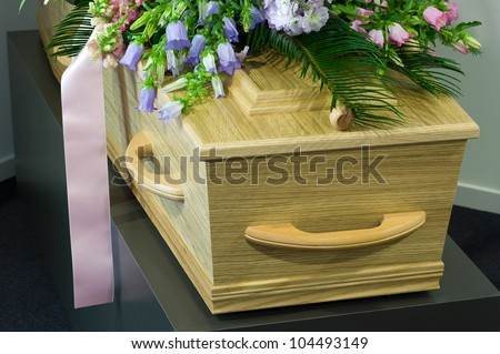 A coffin in a morgue with a flower arrangement - stock photo